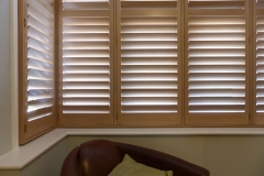 Square Lounge Bay Widow Fitted With Natural Wood Shutters