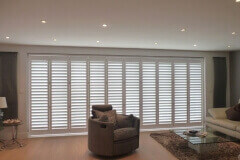White Tracked Shutters on Wide Patio Doors in Living Room
