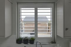 White Plantation Shutters with 89mm Louvres Fitted to Window Above the Kitchen Sink