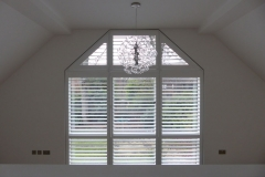 Tall Shaped Window with Custom Made White Shutters Fitted