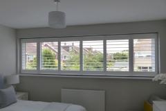 Wide bedroom window with shutters