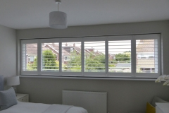 White TPost Shutters Fitted to Wide Window in Bedroom