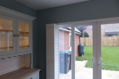 Tracked Bi-Folding Shutters Pushed to Left Side of Wide Patio Doors