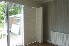 Track Mounted Shutters Partially Closed Over Patio Doors