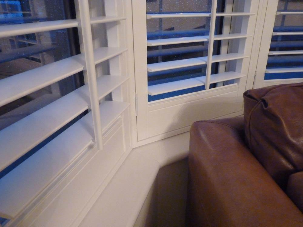 Angle vinyl shutter view around a bay window