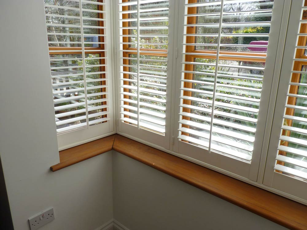 Silk white shutters fitted on a square bay