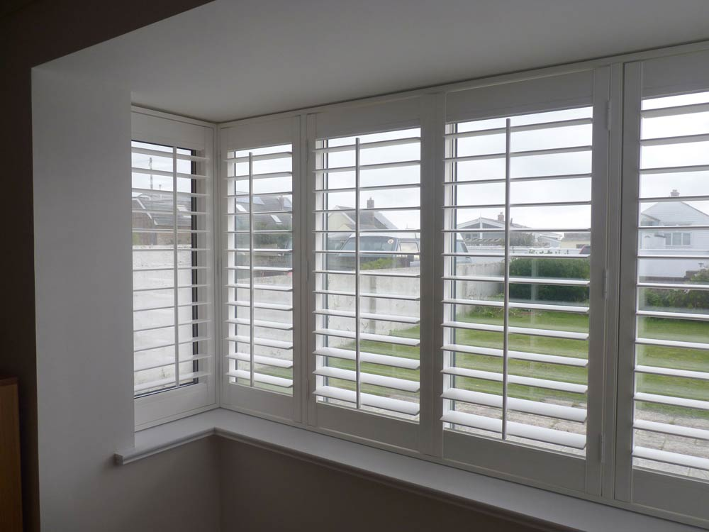 Lounge square bay fitted Vinyl shutters and Tposts