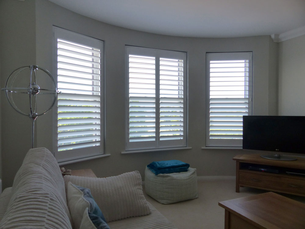 Three Individual Angled Windows in the Lounge Fitted with White Shutters