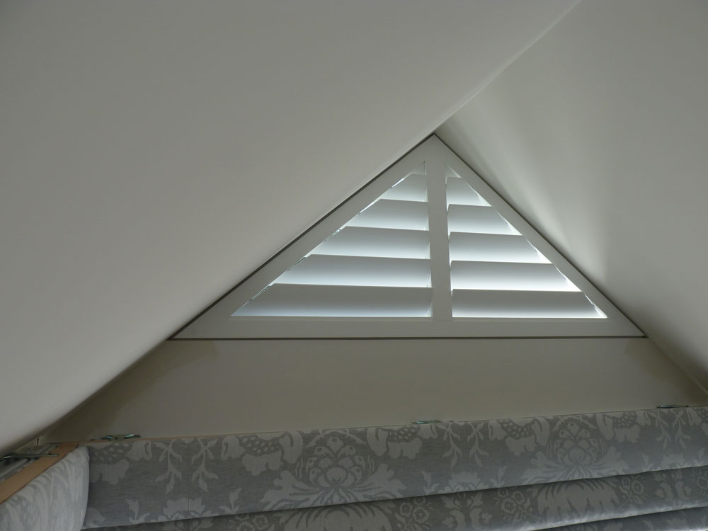 Small Triangle Shape Window with White Wooden Shutters